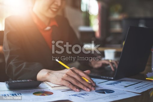 istock Close up Businesswoman hand holding pen and pointing at financial paperwork. 1055474956