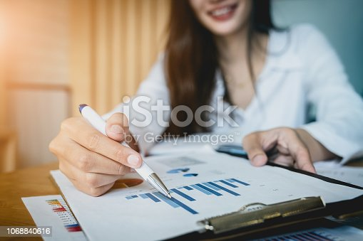 istock Close up Businesswoman hand holding pen and pointing at financial paperwork. 1068840616