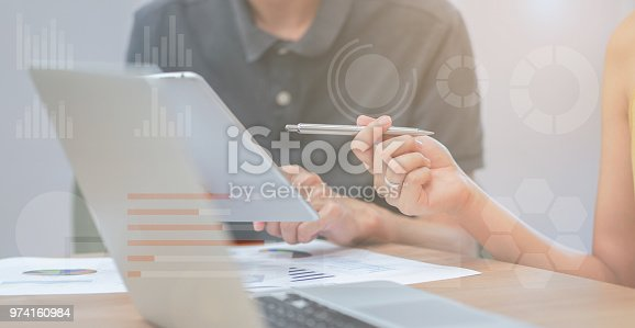 close up businesswoman hand pointing on tablet pad for explaining company profit with colleagues partner with double exposure of statistic chart stock infographic , business technology concept