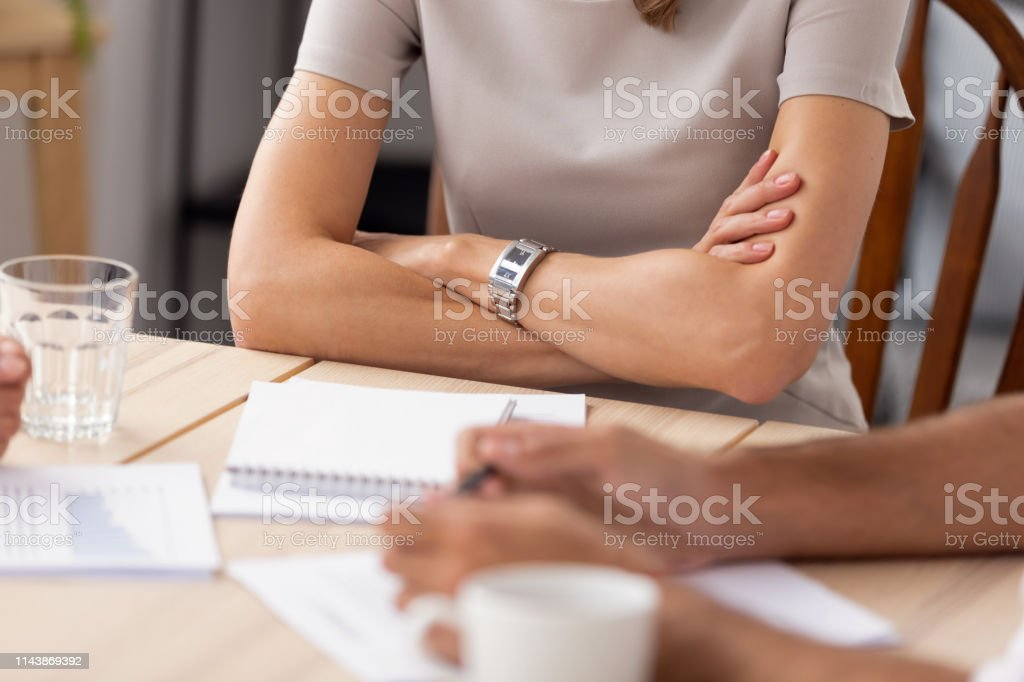 Close up businesswoman with arms crossed sitting at company meeting,...