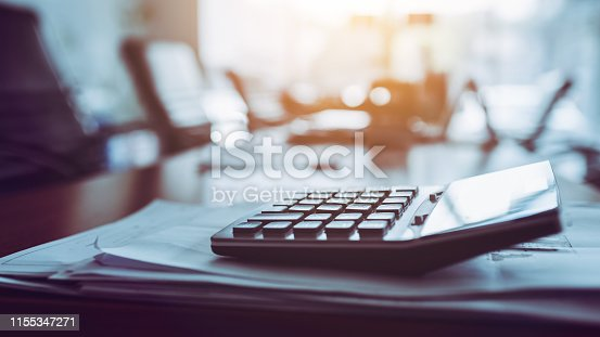 istock Close up calculator on business working desk, dark background. 1155347271