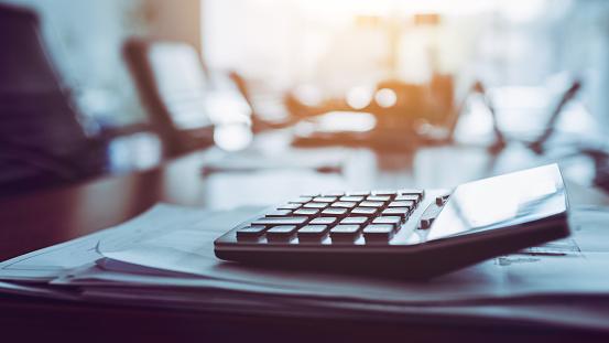 istock Close up calculator on business working desk, dark background. 1155347271
