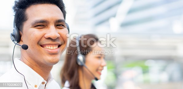 1142008983 istock photo close up call center employee young latin man  wear headset device and smiling with caucasian asian woman colleagues for  telemarketing and help desk concept 1170008022