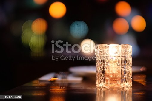 Colorful defocused illuminations, plate and fork. Black background. Bar and restaurant concept