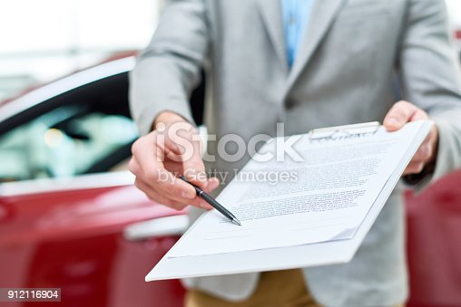939005154 istock photo Close Up Car Salesman Handing Contract to Client 912116904