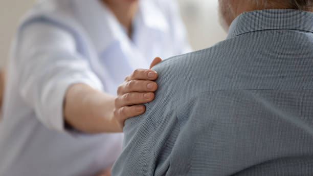 Close up caring doctor touching mature patient shoulder stock photo