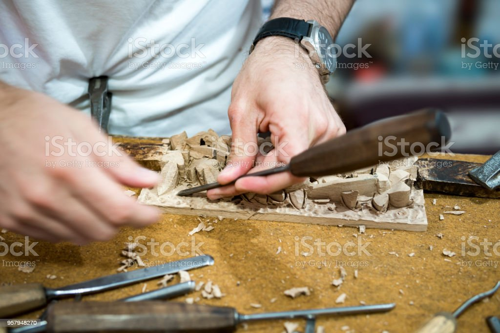Close up carpenter's hands that work with cutter stock photo