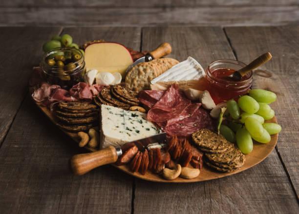 cierre charcutería tabla de carne, queso, galletas sobre mesa de madera. - fuet sausages fotografías e imágenes de stock
