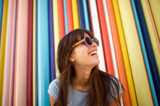 화려한 배경에 선글라스로 웃고 있는 쾌활한 젊은 여성을 닫습니다. - 생활 방식 뉴스 사진 이미지