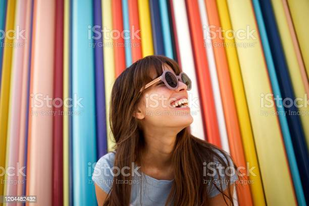 Photo of Close up cheerful young woman laughing with sunglasses against colourful background