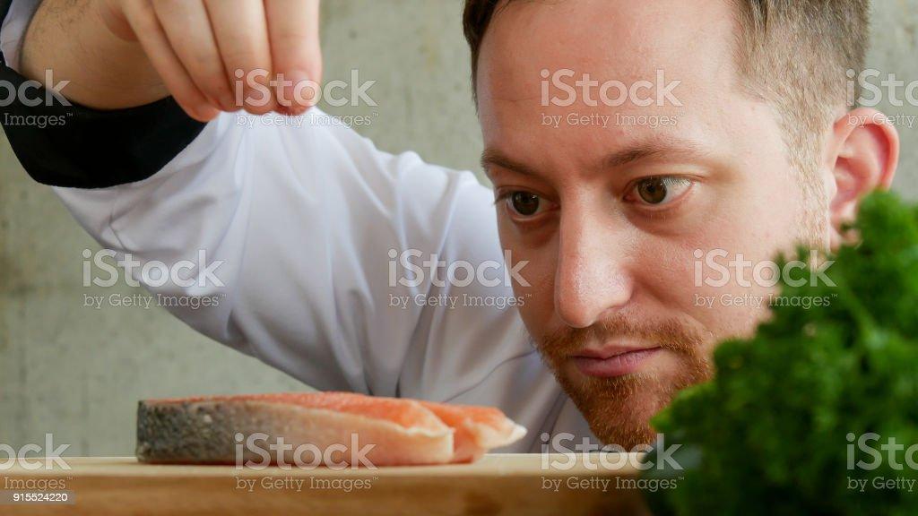 close-up chef colocar sal na fatia de salmão. - foto de acervo