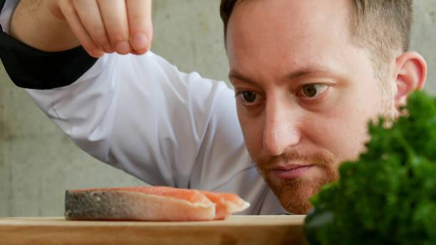 close-up chef colocar sal na fatia de salmão. - fine dining - fotografias e filmes do acervo
