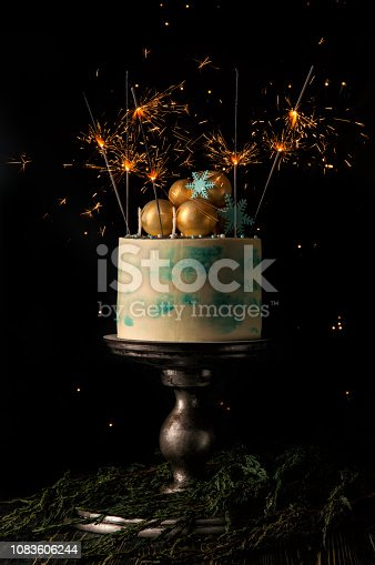 Close up. Christmas cake and many burning sparklers festively decorate it. Dark background with christmas lights. Copy space.