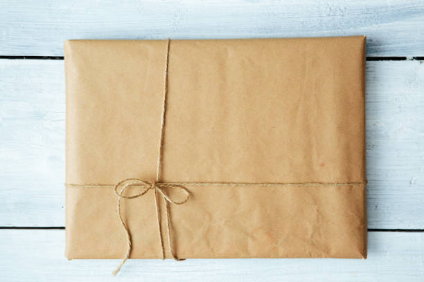 Close up Christmas style rustic brown paper package tied up with strings. White wood floor background. stock photo