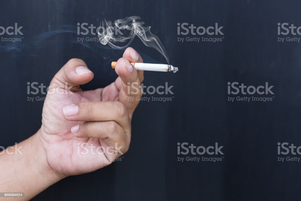 Close up cigarette or tobacco with smoke in hand and copy space'n stock photo
