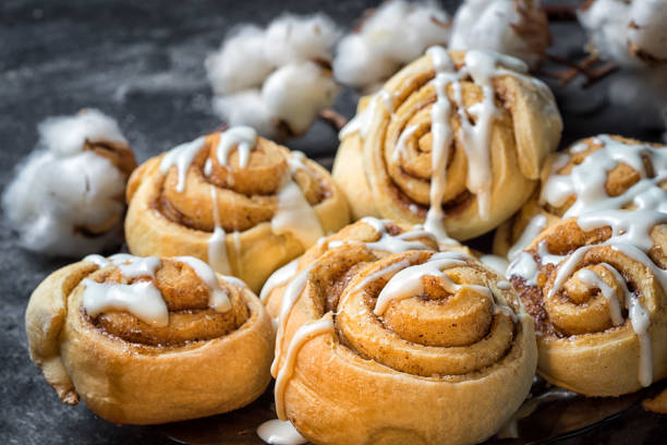 close up cinnamon rolls in a plate, on a dark background with cement cotton boxes behind. close up cinnamon rolls in a plate, on a dark background with cement cotton boxes behind. pastry dough stock pictures, royalty-free photos & images