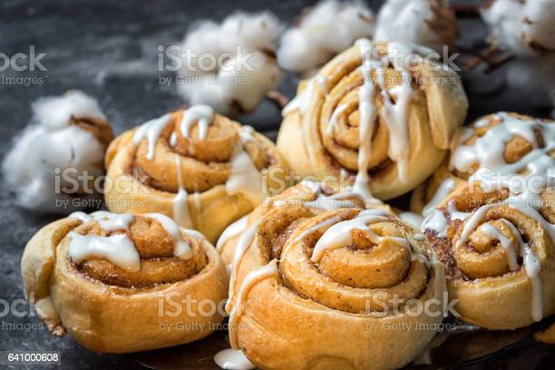 Photo of close up cinnamon rolls in a plate, on a dark background with cement cotton boxes behind.