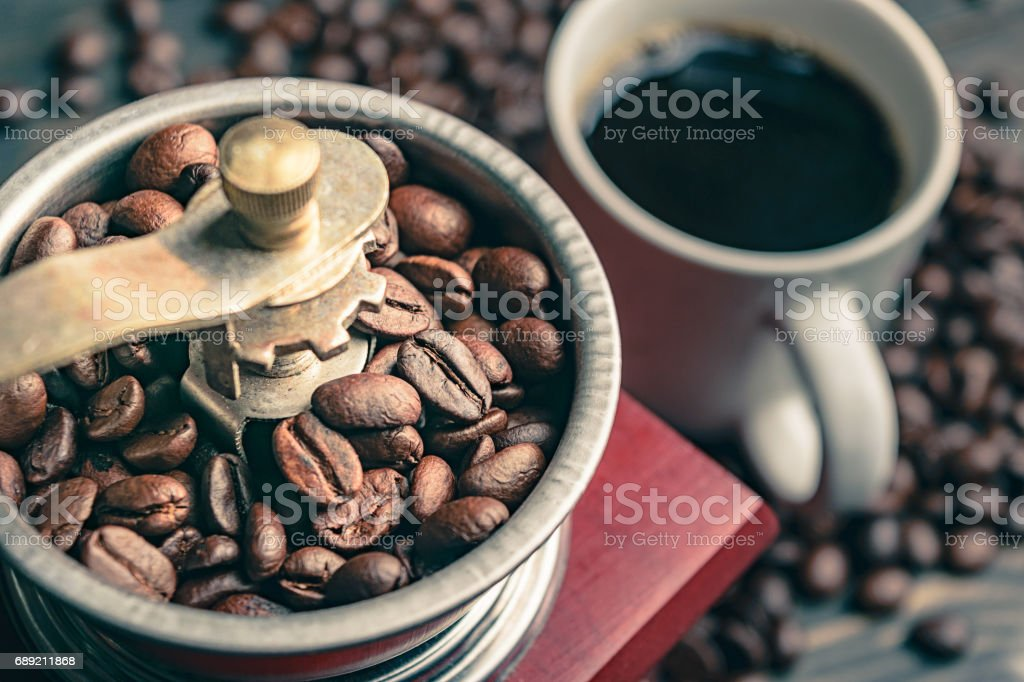 close up coffee bean in grinder and cup stock photo