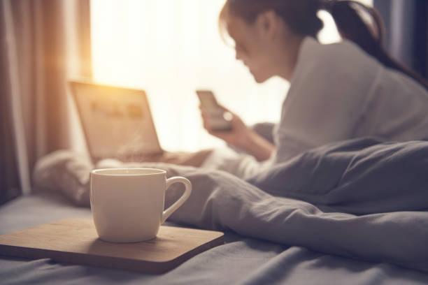 Kaffeetasse und unscharfen Frau aufwachen und die Arbeit mit Laptop und Smartphone hautnah. – Foto