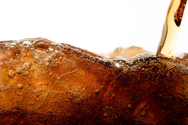 Close up cola pouring with ice and bubble in glass on white background cold drink beverage stock photo