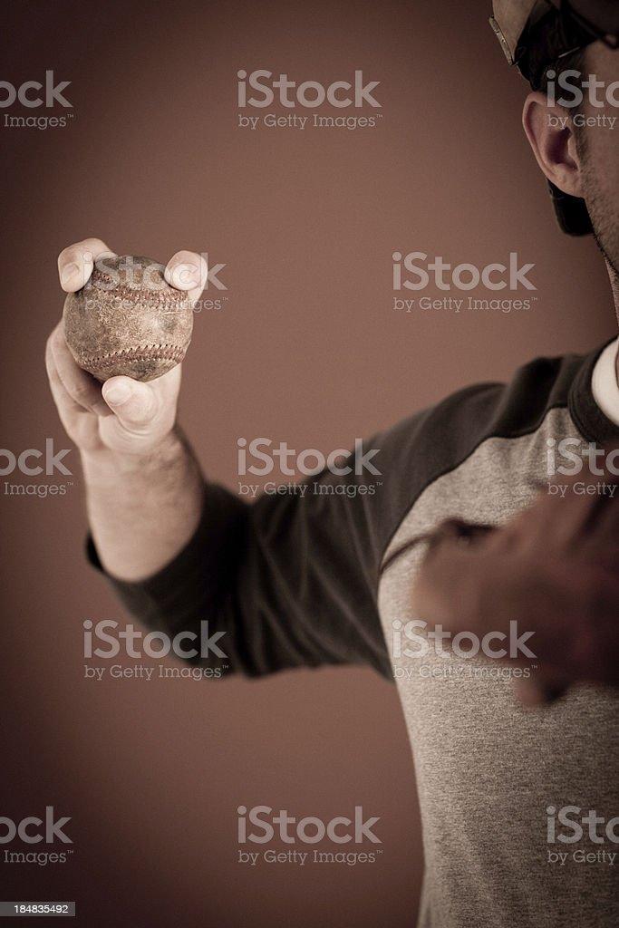 Close up color image of a baseball player holding a vintage baseball....