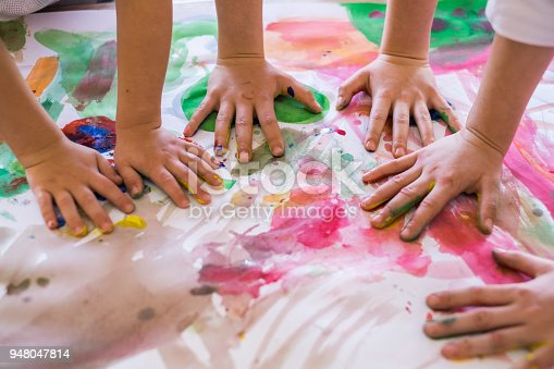 istock Close up colored kids hands on the table 948047814