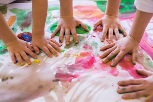 Close up colored kids hands on the table Close up children hands in circle on the table painted with water colors preschool age stock pictures, royalty-free photos & images