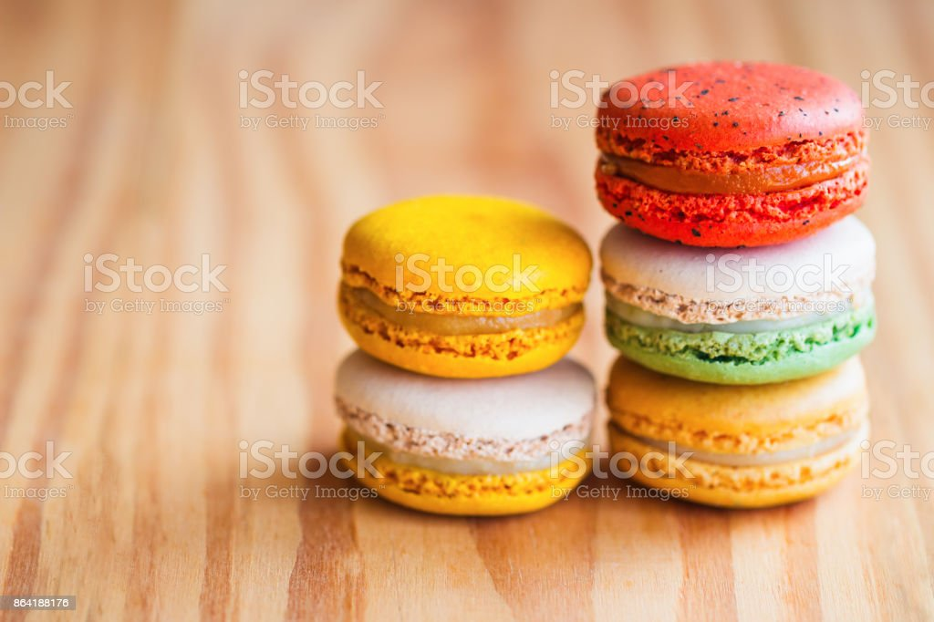 Close up colorful French macaron or Italian macaron. Homemade delicious macaron stack on wood table with copy space for background or wallpaper macro concept. French dessert served with tea or coffee. royalty-free stock photo