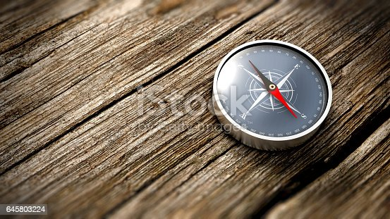 istock Close up compass showing north on a wooden table. 3D Rendering 645803224