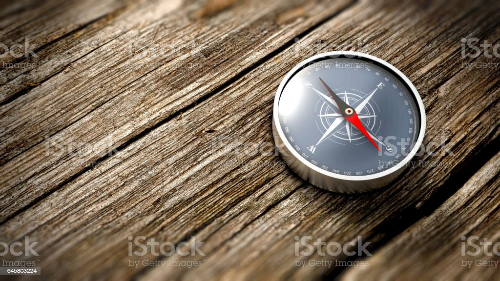 Close up compass showing north on a wooden table. 3D Rendering stock photo