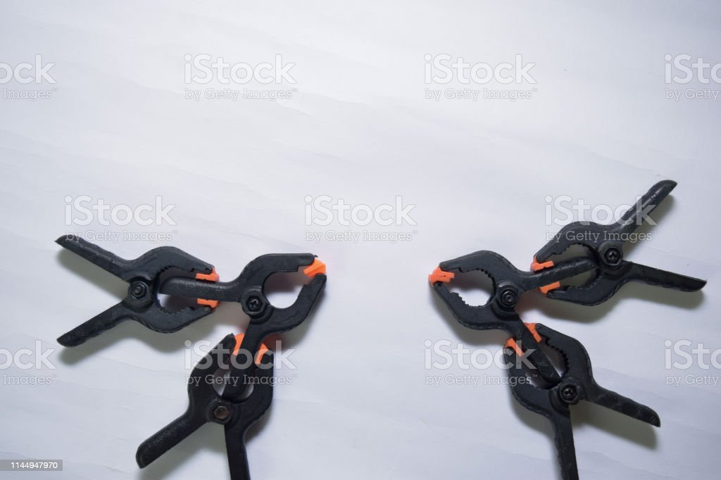 Close up concept black and orange spring clamping isolated on white...