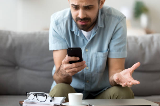 close up confused man having problem with phone, receive bad news - rabbia emozione negativa foto e immagini stock