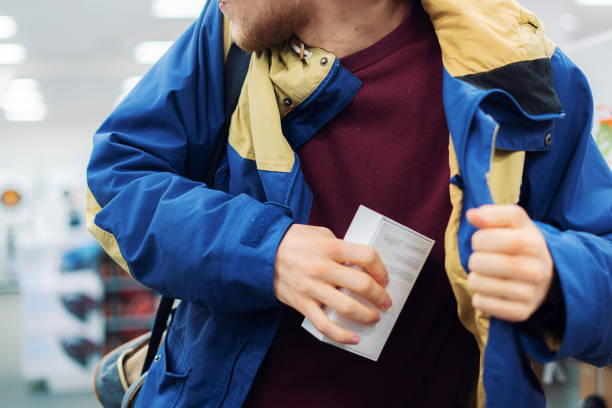 close up consumer  thief's hands putting the new gadget in the pocket in the store stock photo