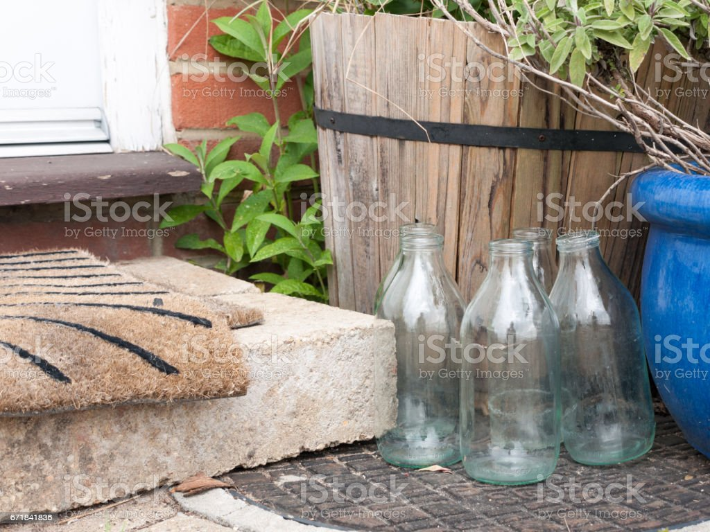 close up cool and modern shot of some glass milk bottles glasses outside empty no milk next to front door step and matt dairy retro vintage food ingredients drink england uk milkman delivery no bottle tops stock photo