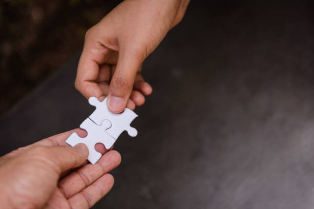 Close up couple hands of man and woman connecting jigsaw puzzle together stock photo