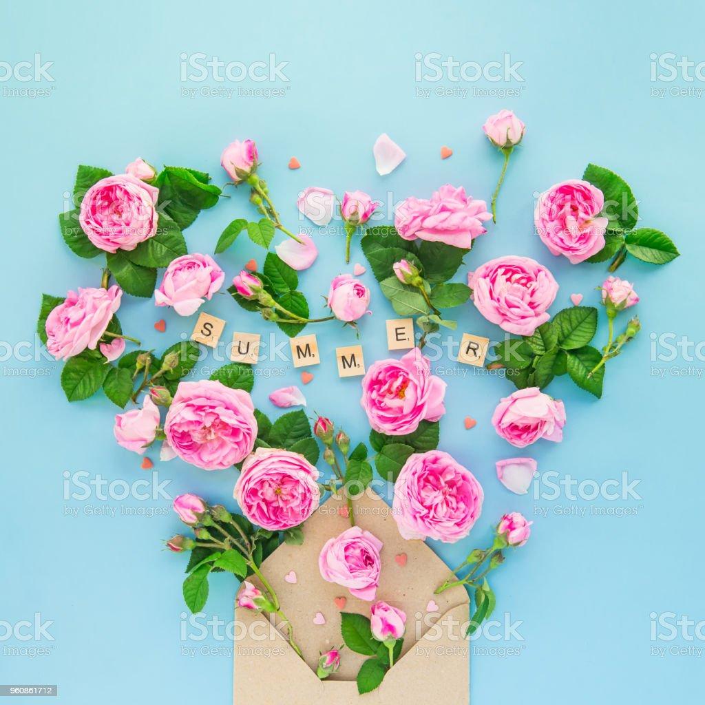 Schließen Sie die kreativen Layout mit Teerose, rosa Blüten, Blätter fliegen aus erfasste Handwerk Papierumschlag in Form von Herzen auf dem blauen Hintergrund. Wort-Summer von Holzbuchstaben. Quadratische Karte. Text-Raum. - Lizenzfrei Baumblüte Stock-Foto