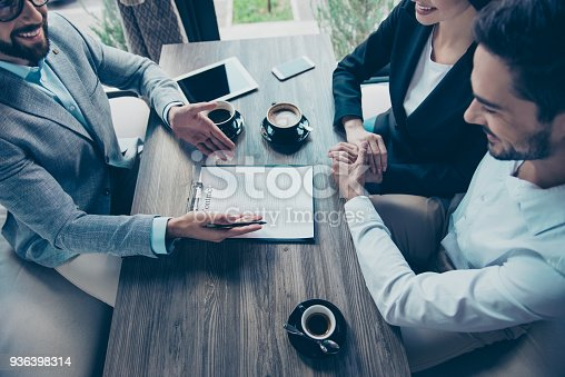 istock Close up cropped high angle photo of young couple reading an agreement of buying a property. Broker giving some advice about new purchase, pointing on contract, to sign it, all are smiling 936398314