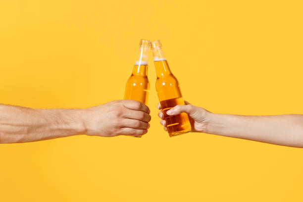 Close up cropped of woman and man two hands horizontal holding lager beer glass bottles and clinking isolated on yellow background. Sport fans cheer up. Friends leisure lifestyle concept. Copy space. Close up cropped of woman and man two hands horizontal holding lager beer glass bottles and clinking isolated on yellow background. Sport fans cheer up. Friends leisure lifestyle concept. Copy space beer alcohol stock pictures, royalty-free photos & images