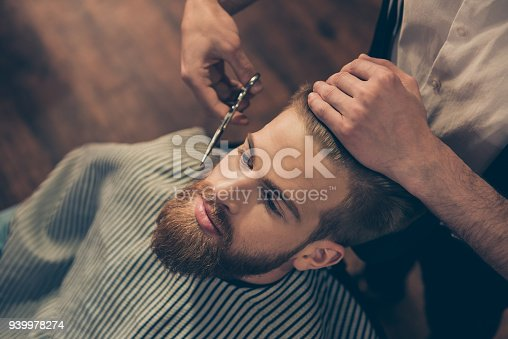 986804130istockphoto Close up cropped photo of a hairdresser`s work for an attractive guy at the barber shop. He is doing styling of his red beard with scissors 939978274