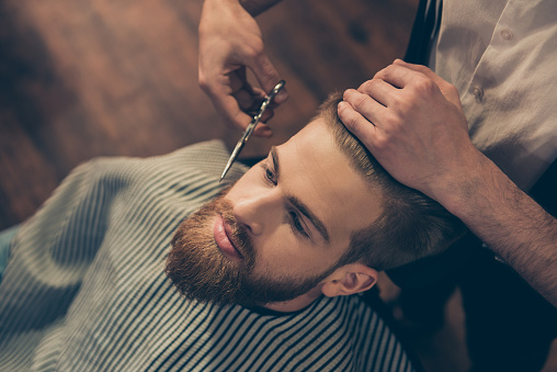 986804130 istock photo Close up cropped photo of a hairdresser`s work for an attractive guy at the barber shop. He is doing styling of his red beard with scissors 939978274