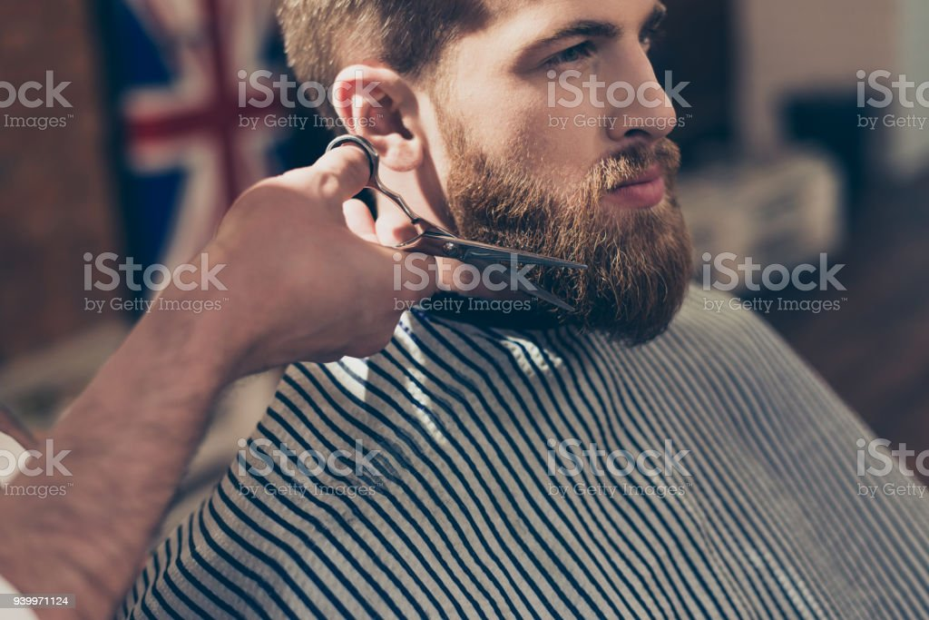 Close up cropped photo of a stylish red bearded guy in a striped cape...