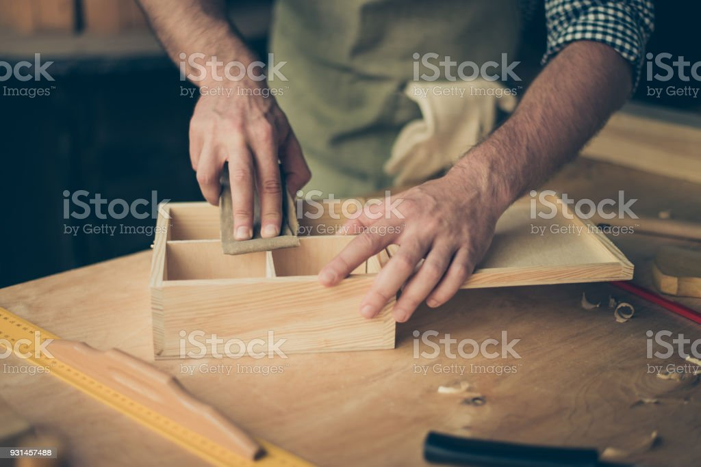 Close up cropped photo of handicraftsman's hands sanding the surface of handmade wooden box with abrasive paper stock photo