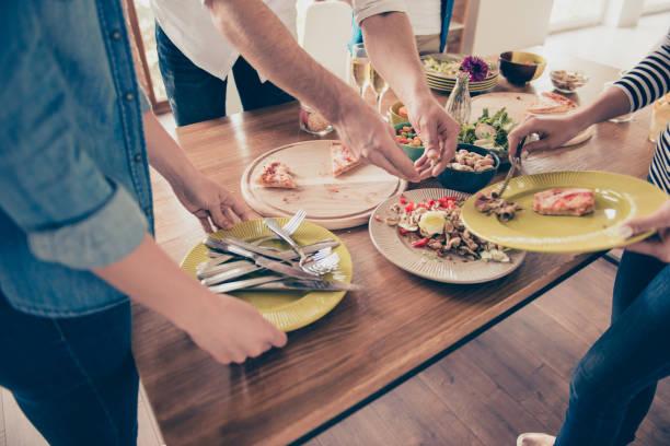 närbild av beskurna fotot människor städa bordet med mat efter fest. de gör det tillsammans, att vara snabbare och roligare - food waste bildbanksfoton och bilder
