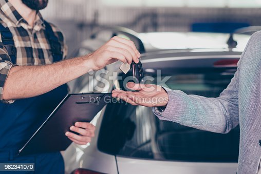 istock Close up cropped photo of professional smart experienced wearing uniform mechanic giving keys back to the owner with license of the fixed car, gray silver automobile is on the blurred background 962341070