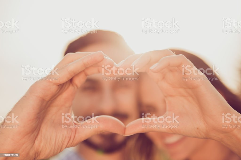 Close up cropped photo of two relaxed carefree cute sweet gentle tender lovely beautiful nice pretty handsome lovers making showing heart people are on blurred background selective focus royalty-free stock photo
