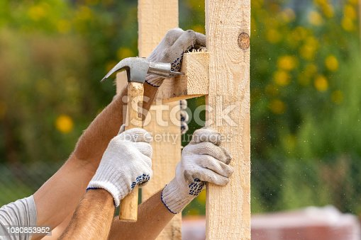 istock Close up cropped photo of two workers in white protective gloves holding plank board installing it on special house hold construction using hammer and nails 1080853952