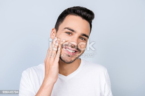 932956896istockphoto Close up cropped portrait of an attractive young brunet man, touching his cheek, wearing white tshirt, standing on light blue background. He is satisfied of styling of his beard 936445794