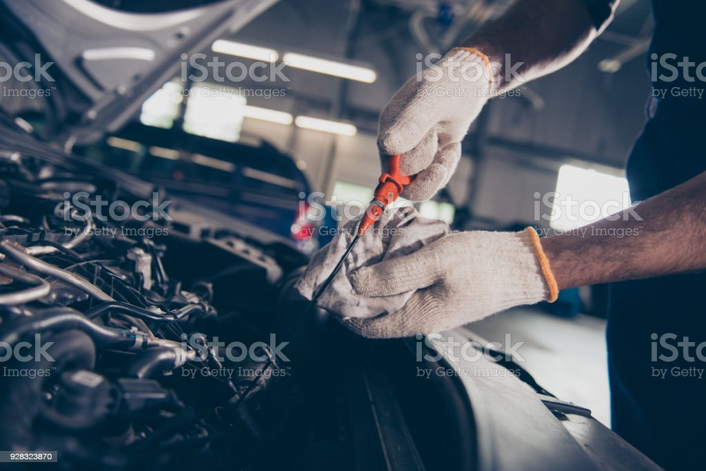 Close up cropped shot of experts mechanical specialist professional checking oil level in car engine with orange tool, in repair shop. Maintenance, safety, open supported hood of auto - foto stock