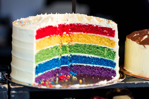 Close up Cross Section of Fresh Rainbow Layer Cake at Food Market Close up color image depicting a cross section of a freshly baked and iced rainbow layer sponge cake on display at a food market. Room for copy space. cake stock pictures, royalty-free photos & images
