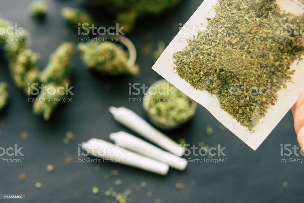 close up crushed weed Joint weed Macro of cannabis buds marijuana and on a black table - Royalty-free Agriculture Stock Photo